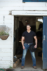 cowboy standing in a horse barn