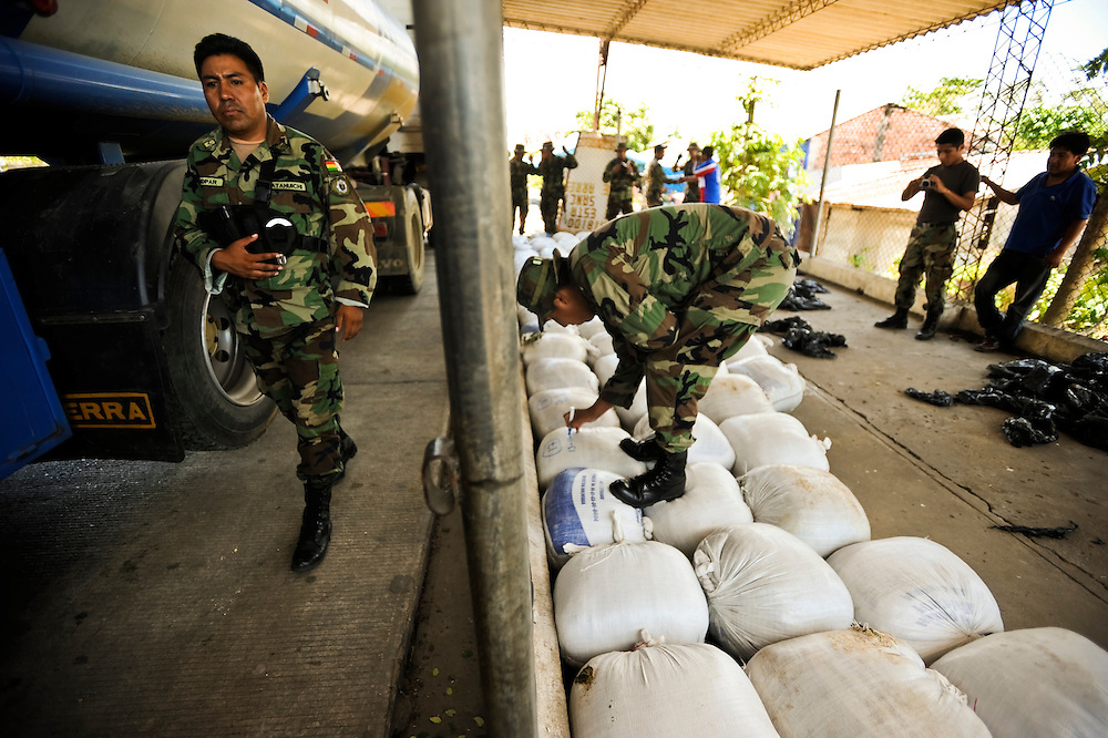"Bolivian FELCN Special Forces count 75 bags of confiscated raw coca found during a raid, along with processing materials to convert it into cocaine-base in Villa Nuevo Horizonte, a dangerous area in the department of Santa Cruz were narcotraffiking runs rampant. FELCN officials report it is the area of Bolivia most thickly dense of narcotraffickers and cocaine-base processing laboratories.  FELCN police commonly referred to it as a ""narco pueblo""."