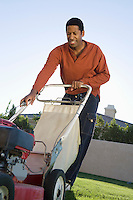Mid-adult man mowing lawn, smiling