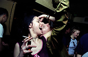 Clubbers dancing, woman smoking a cigarette, UK 2000's