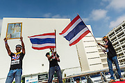 26 NOVEMBER 2013 - BANGKOK, THAILAND: Anti-government protestors hold up a portrait of Bhumibol Adulyadej, the King of Thailand, and wave Thai flags in the courtyard at the Ministry of Finance in Bangkok. Protestors opposed to the government of Thai Prime Minister Yingluck Shinawatra spread out through Bangkok this week. Protestors have taken over the Ministry of Finance, Ministry of Sports and Tourism, Ministry of the Interior and other smaller ministries. The protestors are demanding the Prime Minister resign, the Prime Minister said she will not step down. This is the worst political turmoil in Thailand since 2010 when 90 civilians were killed in an army crackdown against Red Shirt protestors. The Pheu Thai party, supported by the Red Shirts, won the 2011 election and now govern. The protestors demanding the Prime Minister step down are related to the Yellow Shirt protestors that closed airports in Thailand in 2008.     PHOTO BY JACK KURTZ