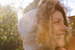 Close up profile of a smiling woman wearing a hooded parka