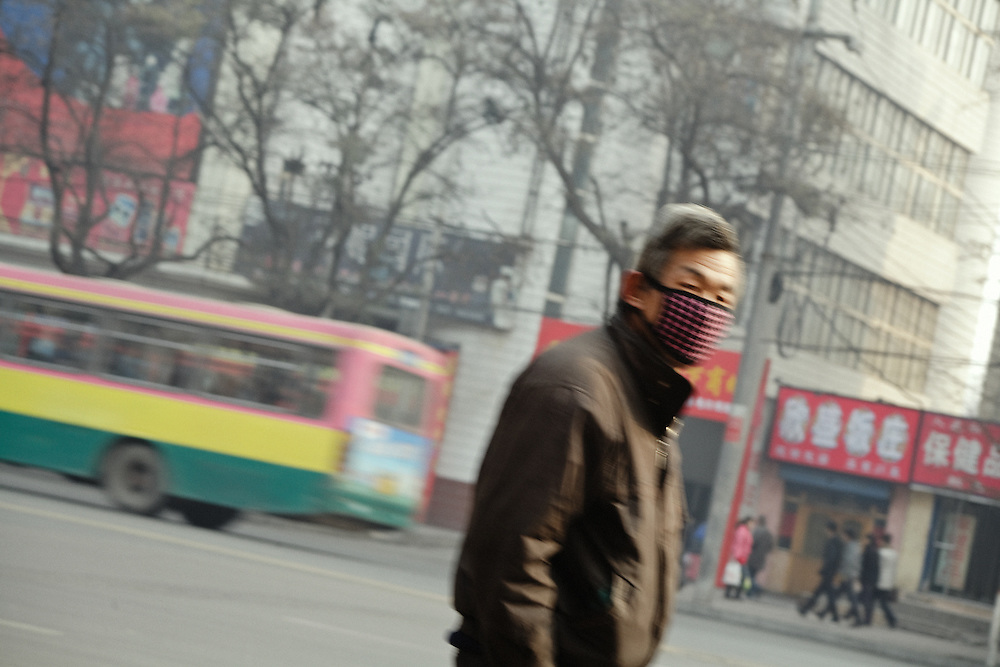 A man wearing a mask against the pollution in the streets of Lanzhou. China.<br /> <br /> -------<br /> Lanzhou, in the Gansu province is the most polluted cities of China and in the world's top ten for atmospheric pollution due to human activity. The town is situated between two hills along the Yellow River and the polluted clouds remain blocked over the town. The sky is most of the time hidden by the pollution.