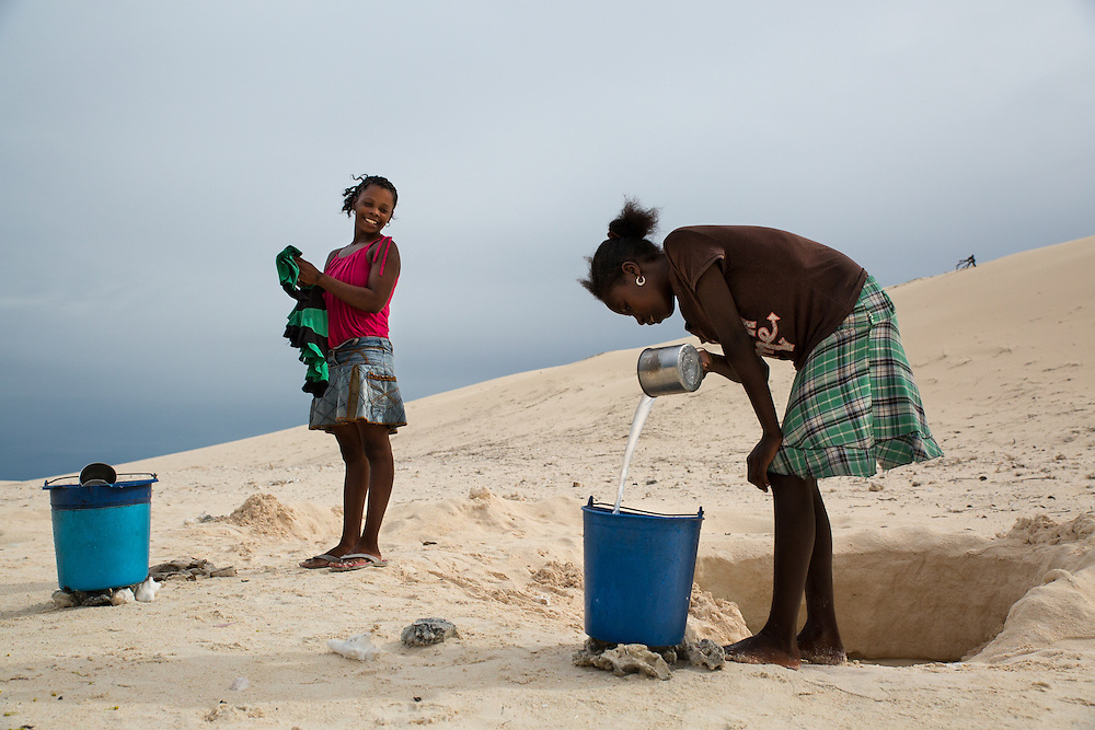 Women collect water from a shallow well in the sand near a village of traditional fishers in south west Madagascar.  Many villages do not have proper wells and fetching clean drinking water is a time-consuming task that women must undertake each day.  Each drop is carefully used. The rural people of south west Madagascar lead fragile lives in a natural environment that is both arid but that can also experience violent cyclones from December to March.  At the same time they depend on coral reef fisheries for food and income.  This makes them among the most vulnerable coastal communities to climate change in the world.