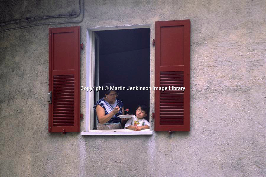 Woman feeding a reluctant child, Italy, August 1999