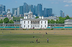 ©Licensed to London News Pictures 21/05/2020<br /> Greenwich, UK. Queen's house and Canary Wharf. People out and about in Greenwich park, Greenwich, London this afternoon enjoying lockdown freedom as the mini heatwave hot weather continues with temperatures set to hit 28C in parts of the UK.  Photo credit: Grant Falvey/LNP