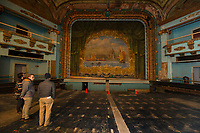 Jared Guilmett and Rick Green view the original 1914 grand drape hanging at the Colonial Theater in downtown Laconia on Monday afternoon.   (Karen Bobotas/for the Laconia Daily Sun)