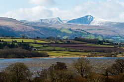 © Licensed to London News Pictures. 12/03/2020. Brecon Beacons, Powys, Wales, UK. Pen-Y-Fan, the highest summit (886 metres) in the Brecon Beacons National Park, Powys, Wales, UK. is seen from across a windswept Llangorse lake today after snow fell on high land in Powys last night. Photo credit: Graham M. Lawrence/LNP