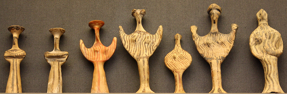 Terracotta female figures wearing a long skirt and a flat head-dress (polos). Made during various times between 1350-1200 BC. Found in Athens and Melos.