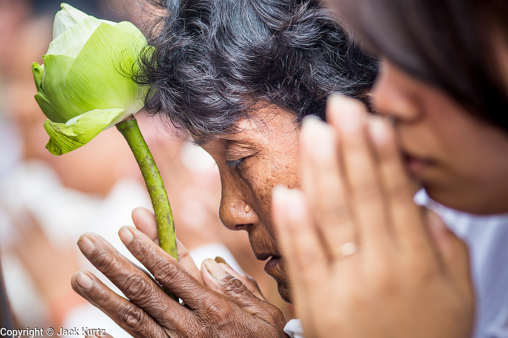 "01 FEBRUARY 2013 - PHNOM PENH, CAMBODIA:  A tear runs down a Cambodian woman's face as the funeral procession of former King Norodom Sihanouk passes her in Phnom Penh. Norodom Sihanouk (31 October 1922 - 15 October 2012) was the King of Cambodia from 1941 to 1955 and again from 1993 to 2004. He was the effective ruler of Cambodia from 1953 to 1970. After his second abdication in 2004, he was given the honorific of ""The King-Father of Cambodia."" Sihanouk died in Beijing, China, where he was receiving medical care, on Oct. 15, 2012. His cremation is will be on Feb. 4, 2013. Over a million people are expected to attend the service.   PHOTO BY JACK KURTZ"