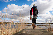 Annandale Way,  Lochmaben. Young woman wearing black jacket, grey wooly hat and beige boots walks on boardwalk next to the water on a cloudy, sunny day.