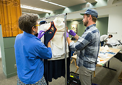 Elizabeth K. Mauro and Scotty Enderle work together on a Norwegian dress with a blouse, apron and purse as part of Registrars to the Rescue (R2R), an initiative of the Washington Museum Association (WaMa), helping create better storage of the Scandinavian Cultural Center historical collection at PLU  Wednesday, June 22, 2016. (Photo: John Froschauer/PLU)