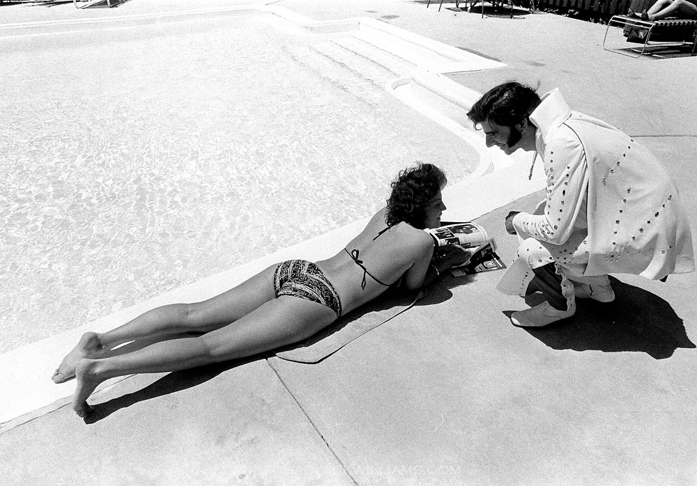 An Elvis Presley impersonator flirts with bikini clad hotel guest while at a Chicago Elvis impersonators convention.