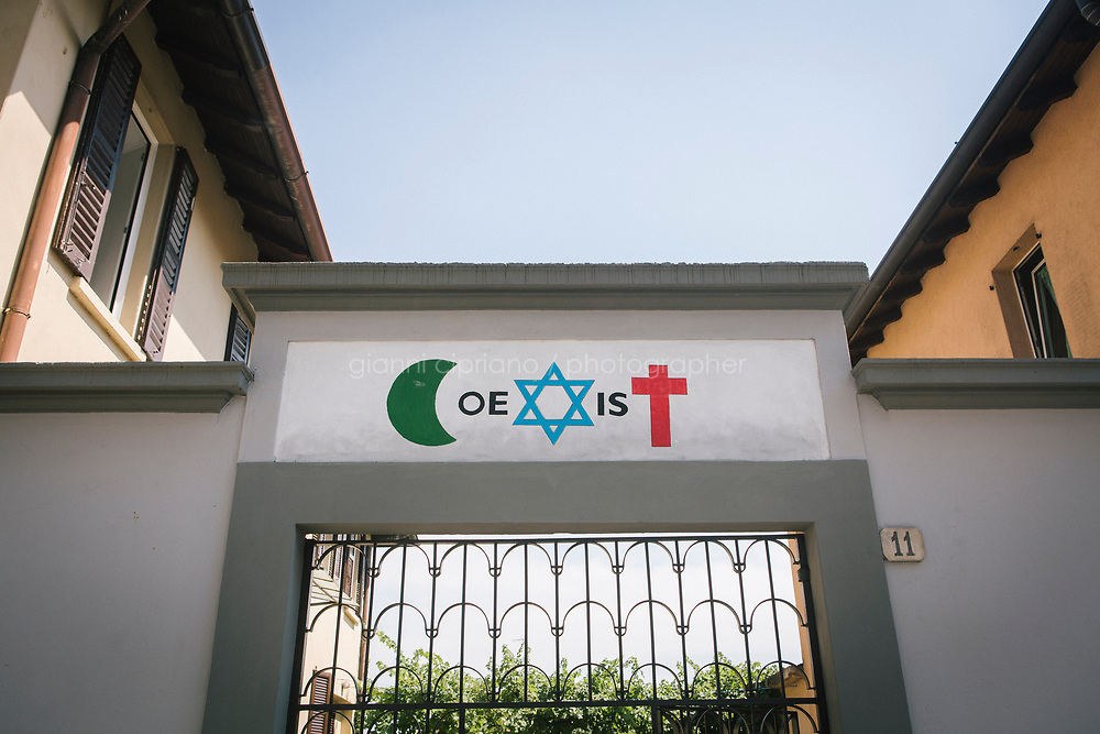 COMO, ITALY - 21 JUNE 2017: The sign &quot;Coexist&quot;, written a crescent moon, a star of David and Christian cross, is seen here at the entrance of the San Martino di Rebbio Parrish, a center on the outskirts of town where more than 50 migrants sleep at night, ran by the local priest Giusto della Valle in Como, Italy, on June 21st 2017.<br /> <br /> Residents of Como are worried that funds redirected to migrants deprived the town&rsquo;s handicapped of services and complained that any protest prompted accusations of racism.<br /> <br /> Throughout Italy, run-off mayoral elections on Sunday will be considered bellwethers for upcoming national elections and immigration has again emerged as a burning issue.<br /> <br /> Italy has registered more than 70,000 migrants this year, 27 percent more than it did by this time in 2016, when a record 181,000 migrants arrived. Waves of migrants continue to make the perilous, and often fatal, crossing to southern Italy from Africa, South Asia and the Middle East, seeing Italy as the gateway to Europe.<br /> <br /> While migrants spoke of their appreciation of Italy&rsquo;s humanitarian efforts to save them from the Mediterranean Sea, they also expressed exhaustion with the country&rsquo;s intricate web of permits and papers and European rules that required them to stay in the country that first documented them.