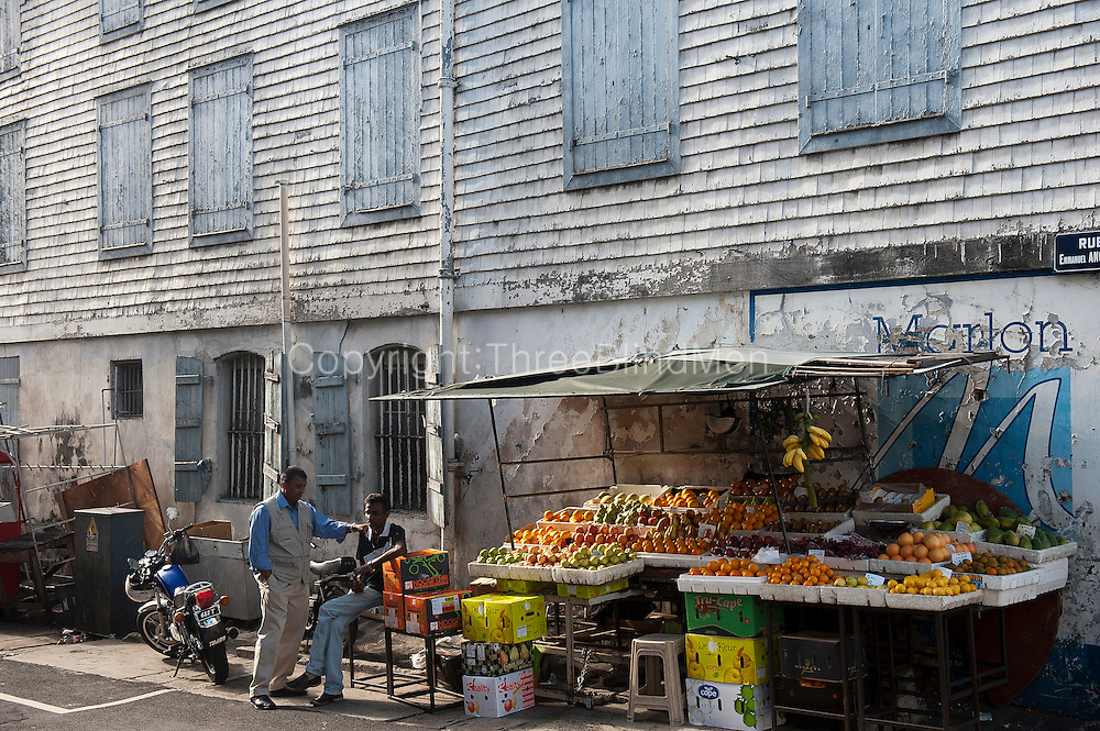 Fine example of an old colonial building in Chinatown with fruit stall set up on the street.
