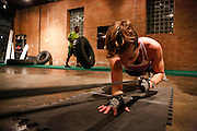 Amy Carenza, 32, pulls on an elastic band while planking to work her core and triceps at the same time at the Psycho Gym in Dallas, Texas, on December 20, 2012.  (Stan Olszewski/The Dallas Morning News)