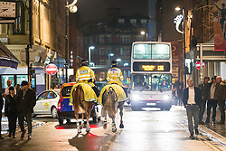 "© Licensed to London News Pictures . 19/12/2014 . Manchester , UK . Mounted police on patrol on Thomas Street . "" Mad Friday "" revellers out in the rain and cold in Manchester . Mad Friday is typically the busiest day of the year for emergency services , taking place on the last Friday before Christmas when office Christmas parties and Christmas revellers enjoy a night out .  Photo credit : Joel Goodman/LNP"