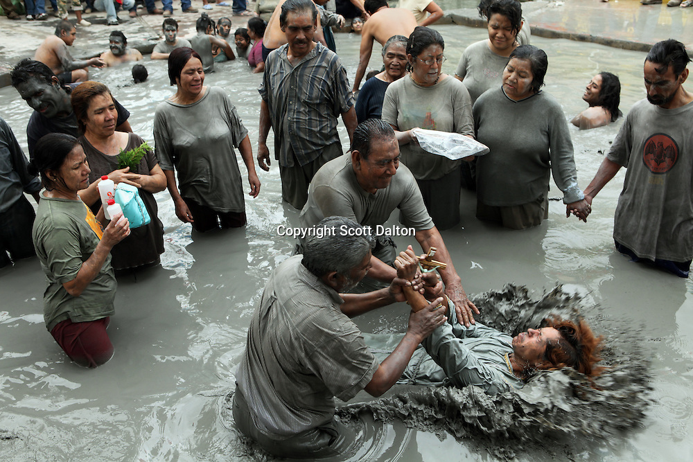 Followers of Nino Fidencio, a faith healer, help to  conduct a ceremony in a mud bath that is believed to have healing properties in Espinazo, Mexico on October 16, 2009. Followers of Nino Fidencio believe that his spirit can posses other healers, who once possessed speak in a child like voice and perform a variety of medical cures on their followers. His believers, an estimated 20,000, gather in his hometown for a three-day festival twice a year in March and October. (Photo/Scott Dalton)