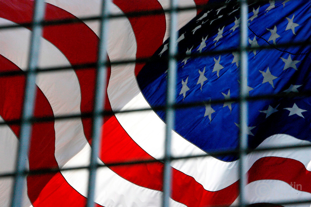 epa00812542 An American flag on the site of the World Trade Center tower is seen through a fence on Thursday, 24 August 2006. Five years after the terrorist attack of 11 September 2001, developers and politicians are still finalizing plans for the site and memorial.  EPA/JUSTIN LANE
