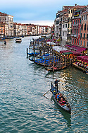 Iconic Venice Italy. A Gondolier paddles lovers up the Grand Canal in Venice Italy at sunset.