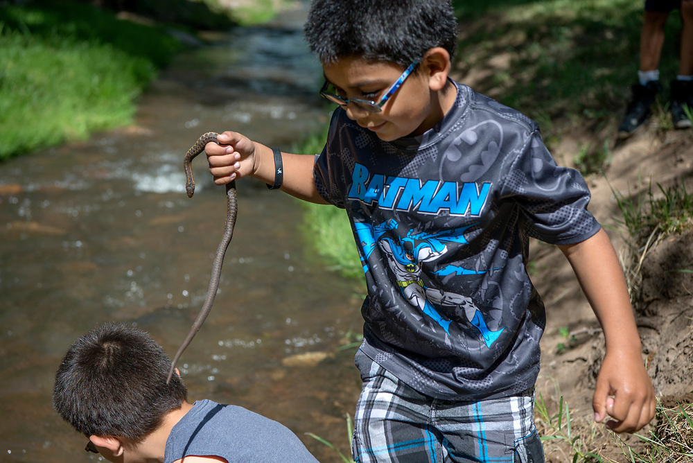 em060217c/a/Izik Chavez, 10, left, and his brother Isaiah Chavez 8, look for fish and water snakes along the Santa Fe River near the State Land Office in Santa Fe, Friday June 2, 2017. This was after 500, 9 to 11 inch rainbows trout were stocked in the river for the Santa Fe Kid's Fishing Derby Saturday morning. The derby opens at 7 a.m. for kids 11 and under. After noon everyone is encouraged to fish. There will also be raffle tickets available for the kids to win several donated prizes.  (Eddie Moore/Albuquerque Journal)