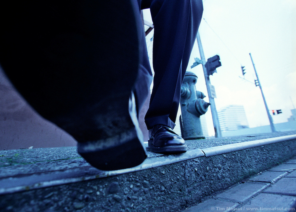 A man in a business suit steps off the curb.