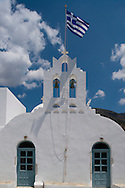 A Greek flag flying over Taxiarxes Church in Vathi, Sifnos, The Cyclades, Greek Islands, Greece, Europe
