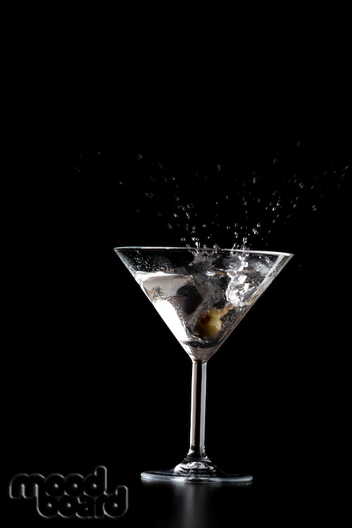 Splash in mrtini glass on black background