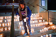 22 DECEMBER 2011 - PHOENIX, AZ:   A child picks up a candle to carry during a march against sexual violence in Phoenix. About 300 people marched through downtown Phoenix Thursday night in a silent candle lit procession to protest against the way the Maricopa County Sheriff's Department, led by Sheriff Joe Arpaio, has conducted sexual assault and rape investigations. Two recent media reports, one by the East Valley Tribune, a newspaper in Mesa, AZ, and one by the Associated Press concluded that the Sheriff's department has bungled more than 430 rape investigations. Last week, a US Department of Justice report cited the unresolved rape investigations along with evidence of wide spread racial profiling by the sheriff's department in a report that was highly critical of Sheriff Arpaio and the Sheriff's Department.     PHOTO BY JACK KURTZ