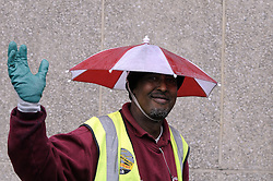 © Licensed to London News Pictures. 11/10/2013<br /> Wet rainy weather today (11.10.2013)  Tower Hill,London. <br /> This Tower Hamlets street cleaner named Omar is enjoying the rain with his head umbrella on as he works outside Tower Hill Station,London.<br /> Photo credit :Grant Falvey/LNP