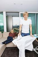 Man ironing shirt while woman sitting on sofa at home