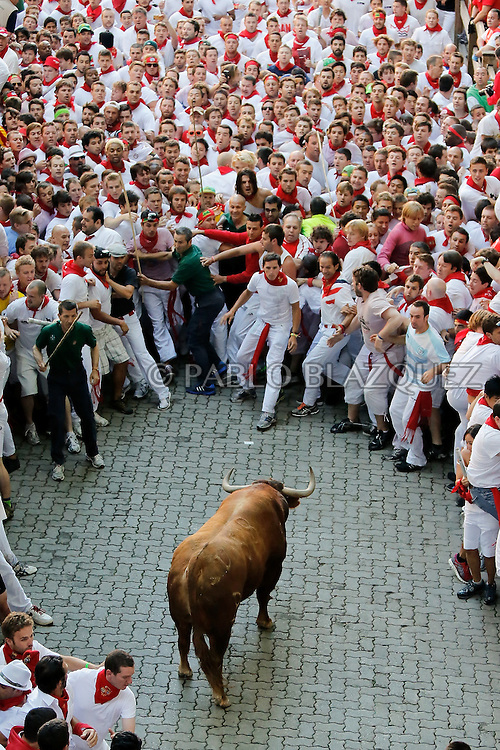 PAMPLONA, SPAIN - JULY 07: An Alcurrucen's ranch fighting bull stands alone surrounded by a crowd of runners on the way to entering the bullring during the second day of the San Fermin Running Of The Bulls festival, on July 7, 2013 in Pamplona, Spain. The annual Fiesta de San Fermin, made famous by the 1926 novel of US writer Ernest Hemmingway 'The Sun Also Rises', involves the running of the bulls through the historic heart of Pamplona, this year for nine days from July 6-14.  (© Pablo Blazquez)