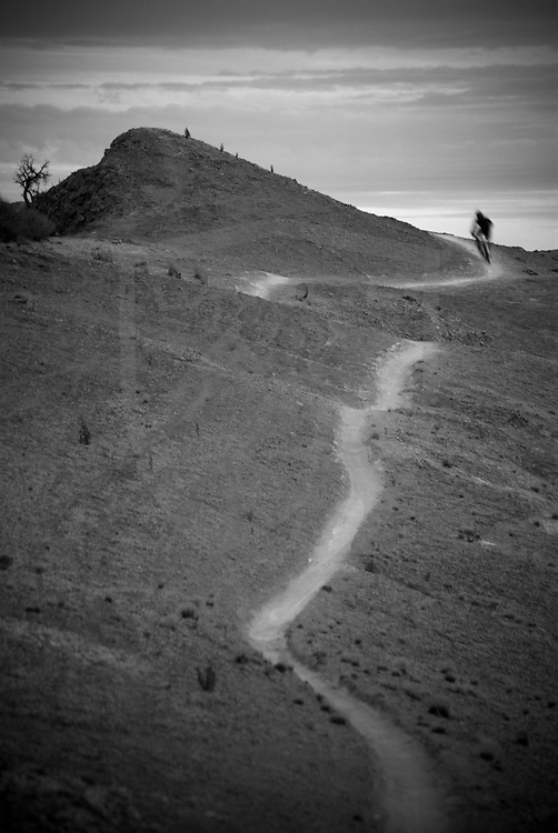 rider kevin lange on the deep gray of white mesa singletrack, new mexico
