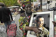 Belgie, Brussel, 28-7-2011Rommelmarkt. Een afrikaanse vrouw kocht een gesigneerd portret van Elvis Presley. Zij verwacht dat dit veel waard is vanwege de handtekening....Marche aux puces at Jeu de Balles Flea market at Vossenplein in Marollen wijk.  Foto: Flip Franssen/Hollandse Hoogte