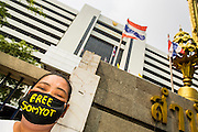 "23 JANUARY 2013 - BANGKOK, THAILAND: A supporter of Somyot Prueksakasemsuk wears a gag to show his support for the convicted magazine editor. Somyot was sentenced to 11 years imprisonment for ""Lese Majeste"" violations Wednesday. He was arrested on April 30, 2011, and charged under article 112 of Thailand's penal code, which states that ""whoever defames, insults or threatens the King, the Queen, the Heir-apparent or the Regent, shall be punished with imprisonment of three to fifteen years"" after the magazine he edited, ""Red Power"" (later changed to ""The Voice of Thaksin"") published two articles by Jit Pollachan, the pseudonym of Jakrapob Penkair, the exiled former spokesman of exiled fugitive former Prime Minister Thaksin Shinawatra. Jakrapob, now living in Cambodia, has never been charged with any crime for what he wrote.       PHOTO BY JACK KURTZ"