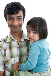 Portrait of a father holding his daughter in the studio,