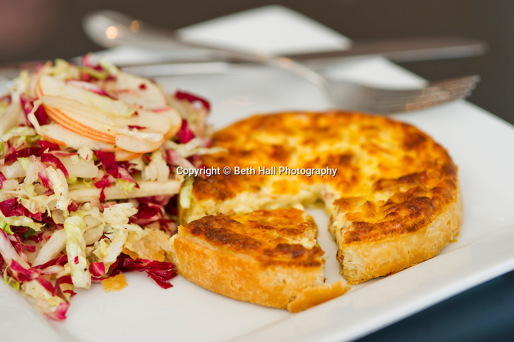 An individual Quiche Lorraine served with a cabbage salad..