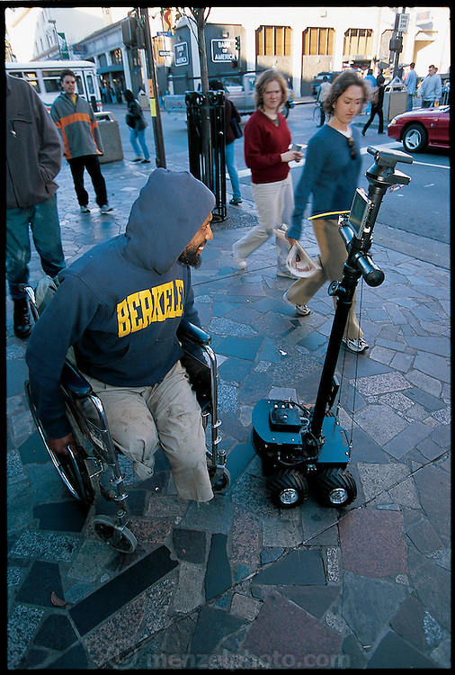 "On a test run on Telegraph Avenue, a busy retail street near the UC Berkeley campus, Paulos controls the ProP (Personal Roving Presence) from a short distance away, via a remote link. One amused man in a wheelchair even stops and asks it for a light. Berkeley graduate student Eric Paulos describes his (PRoP) as ""a simple, inexpensive, Internet-controlled, untethered tele-robot that strives to provide the sensation of tele-embodiment in a remote real space."" Berkeley, CA. From the book Robo sapiens: Evolution of a New Species, page 169."