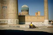August 2008 - Samarcande, Uzbekistan. A yellow-dressed girl jump from the wall of the Bibi Khanoum mosque.
