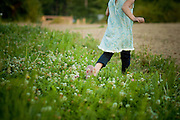 Girl running thru a field of wildflowers.