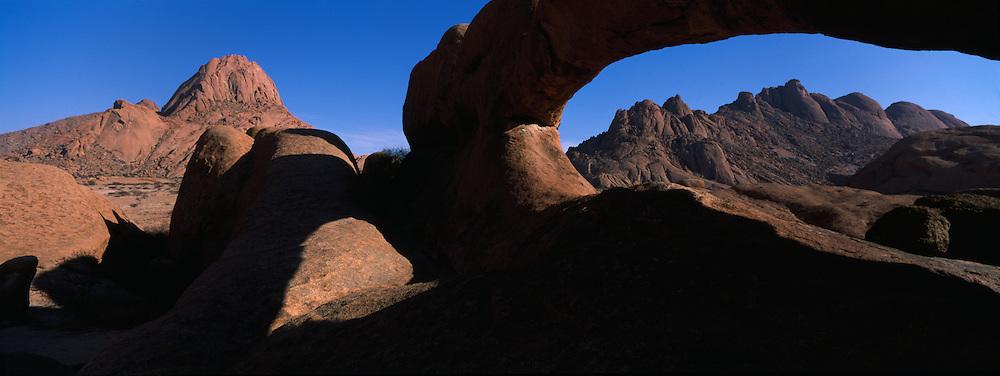 Africa, Namibia, Usakos, Morning sun lights natural granite arch overlooking Spitzkoppe rock formation in Namib Desert