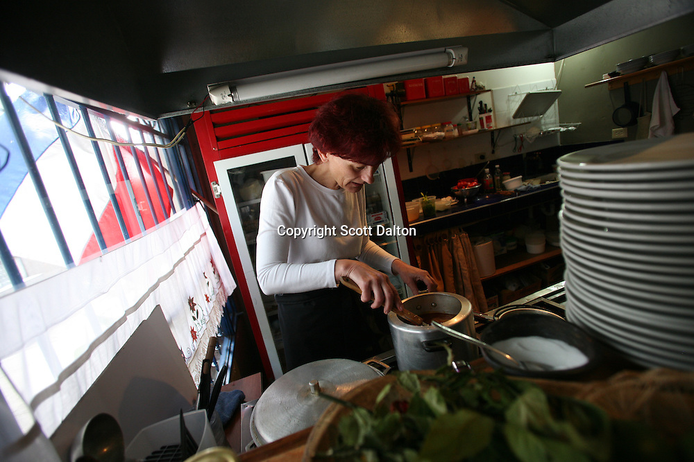 Katarina Markovich, a Serbian war refugee, prepares a meal at her restaurant Beograd, located in La Macarena neighborhood in Bogotá, Colombia on Sunday, July 12, 2009. La Macarena has slowly been transforming from a rough neighborhood into a trendy hangout for locals and expats. (Photo/Scott Dalton)