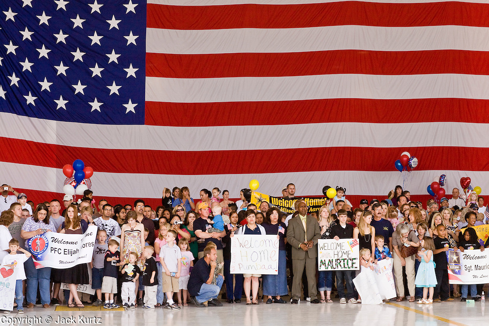 """30 MARCH 2008 -- PHOENIX, AZ: The family members of Arizona National Guard soldiers wait for their loved ones to come home from Afghanistan in an Air Force hanger in Phoenix, AZ, Sunday. About 250 members of the Arizona Army National Guard's 158th Infantry Battalion returned to Phoenix, AZ, from a year long deployment in Afghanistan Sunday. The unit, also known as the """"Bushmasters"""" from their service in World War II, was part of the largest single-unit deployment of the Arizona National Guard since the second World War. Two members of the battalion were killed in action during their deployment. The battalion, a combat unit, engaged in counter insurgency operations through out their deployment. Photo by Jack Kurtz / ZUMA Press"""