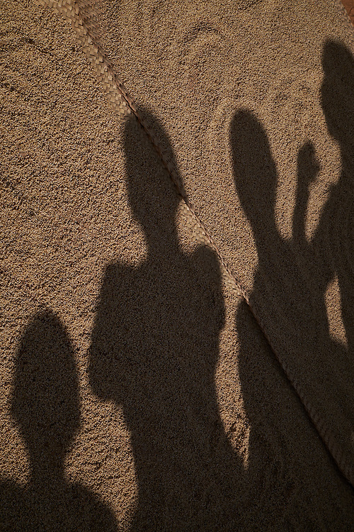 Shadows of children are cast on drying grain at a camp of internally displaced people near the village of Kouble by the side of the road on the highway outside of Diffa, Niger on February 17, 2016. The camp is made up of displaced people and refugees from villages along the border between Niger and Nigeria and who fled attacks from Boko Haram. Many of those who fled were farmers along the nearby border. The men will return during the day to tend fields in their villages that have not been burnt or pillaged by Boko Haram.
