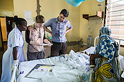 Dr Siobhan Neville and Dr Peter O'Reilly examine patients notes on the Intensive care ward during the daily rounds. St Walburg's Hospital, Nyangao. Lindi Region, Tanzania.