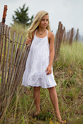 little girl in a white dress standing by a wooden beach fence in East Hampton, NY