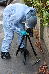 © Licensed to London News Pictures. 05/08/2018. LONDON, UK. A forensics officer photographs the scene of a knife found in Norbiton Avenue, close to the police cordon in Cambridge Gardens, Kingston-Upon-Thames.  A murder investigation has been launched after a man in his 20s was fatally stabbed in Cambridge Gardens in the early hours of Sunday morning.   Investigations are ongoing  It is not known whether the knife found in Norbiton Avenue is related to the murder investgation.  Photo credit: Stephen Chung/LNP