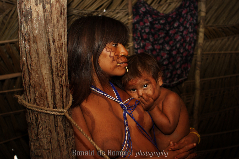 Viriunaveteri, Venezuela. Yanomami mother and child inside a hut..The village of Viriunaveteri consists of 15 huts around a muddy square. It's situated in the Venezuelan Amazone several days by boat from the nearest town. This community on the banks of the Casiquiare is one of the few Yanomami villages that actually has some contact with the outside world. Most other tribes live deeper in the jungle.
