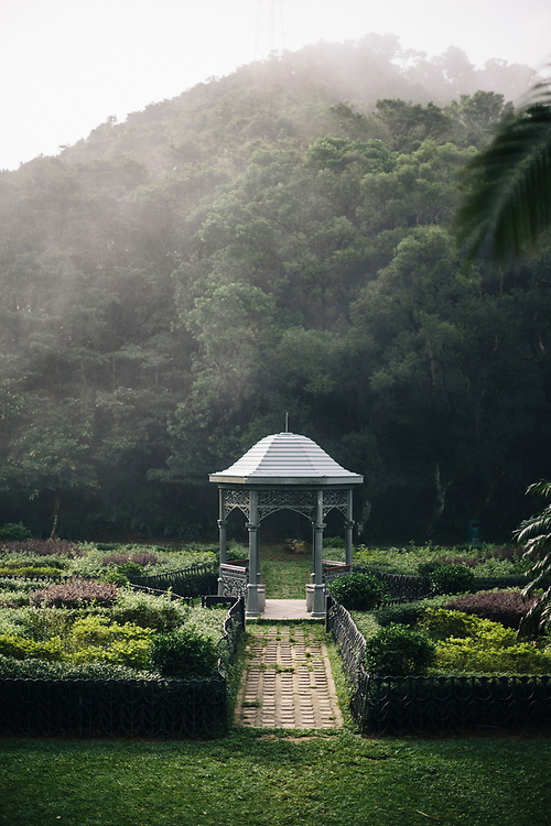 A gazebo in a green field near the top of Hong Kong's The Peak.