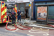 Firemen pump out water from basements following a burst water main which closed the otherwise busy junction of Half Moon Lane and Dulwich Road in the south London area of Herne Hill. Emergency services were called at about 5am, when water inundated local businesses, forcing shopkeepers and owners to evacuate their properties and leave before electricity supplies were shut down. Copyright Richard Baker / Alamy Live News.